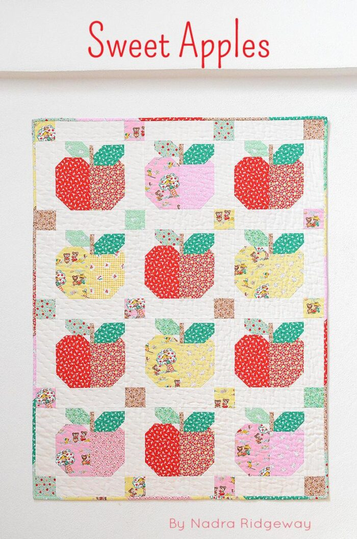 Apple quilt pattern in reds and yellows on white wall