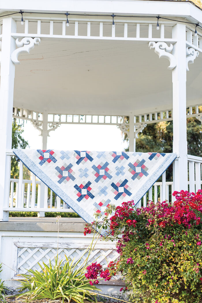 red white and blue quilt in white gazebo