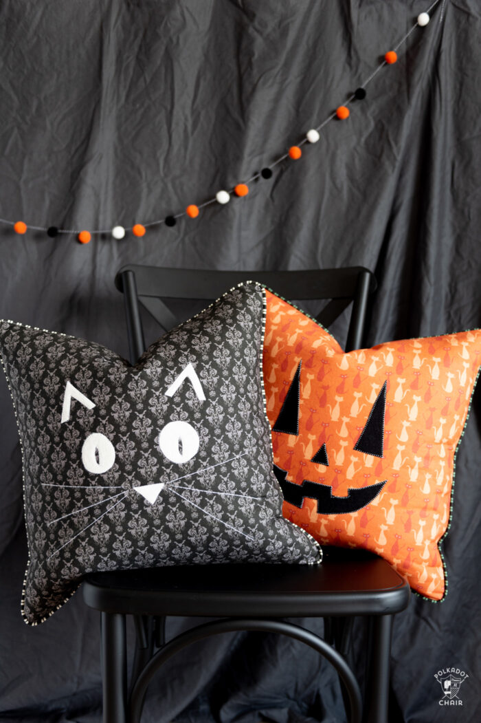 orange pumpkin pillow on black chair in front of gray wall