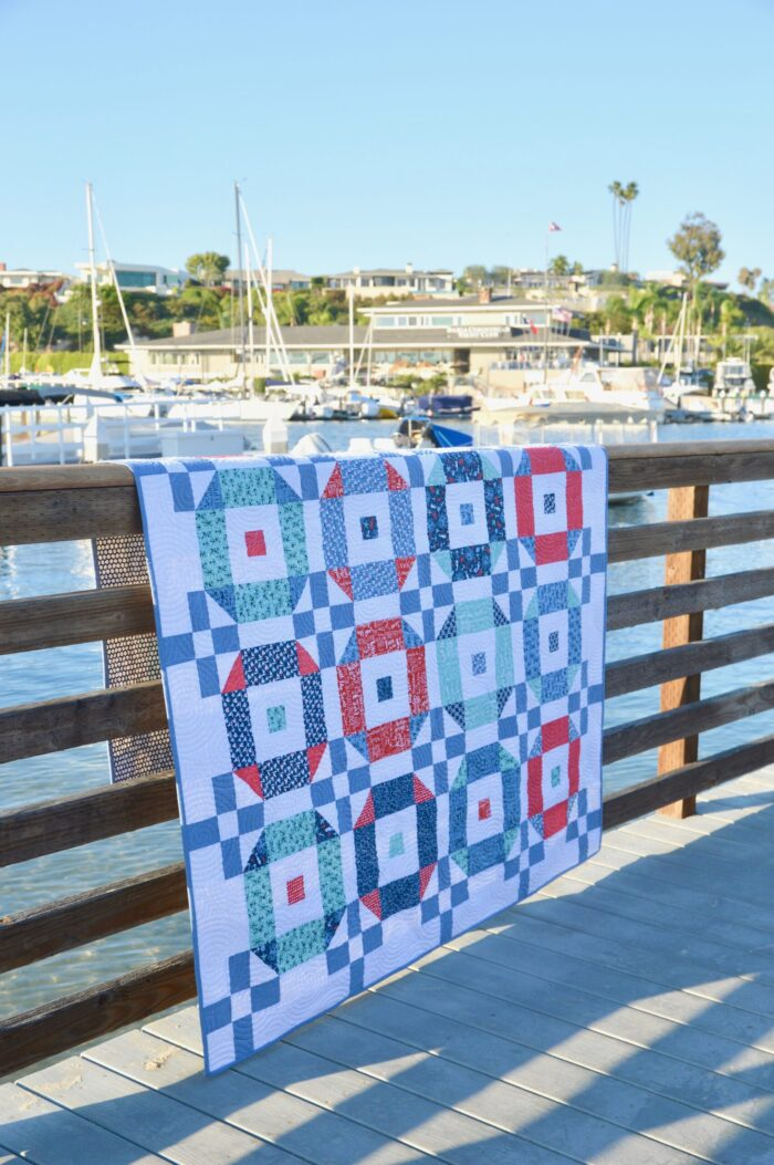 red white and blue quilt on fence at waterfront