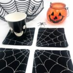 4 black and white spiderweb coasters on white table with halloween props