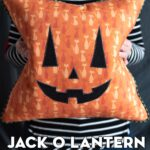 woman holding orange pumpkin pillow