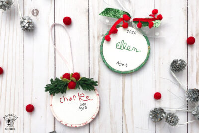 hand embroidered christmas ornaments with childrens names on white wood table