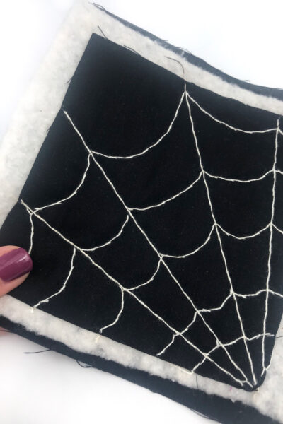 black fabric with a white spiderweb stitched with white thread on white table