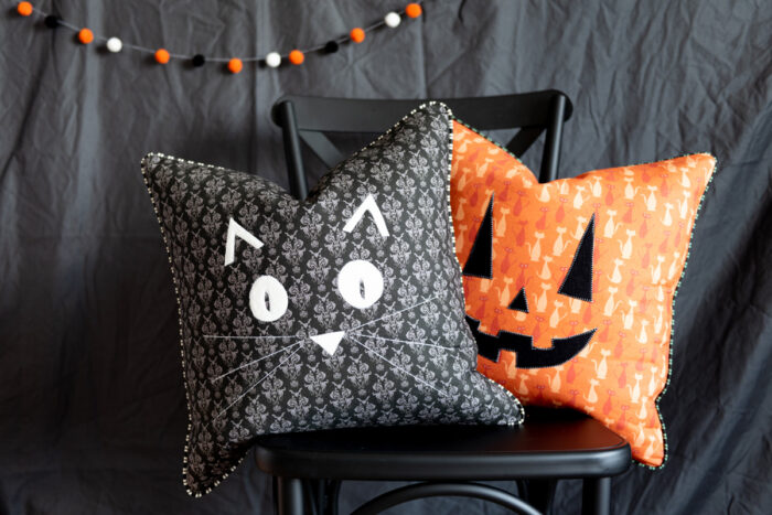 halloween pillows on black chair