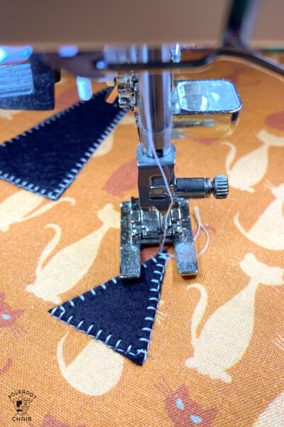 close up of sewing machine foot sewing applique stitches.