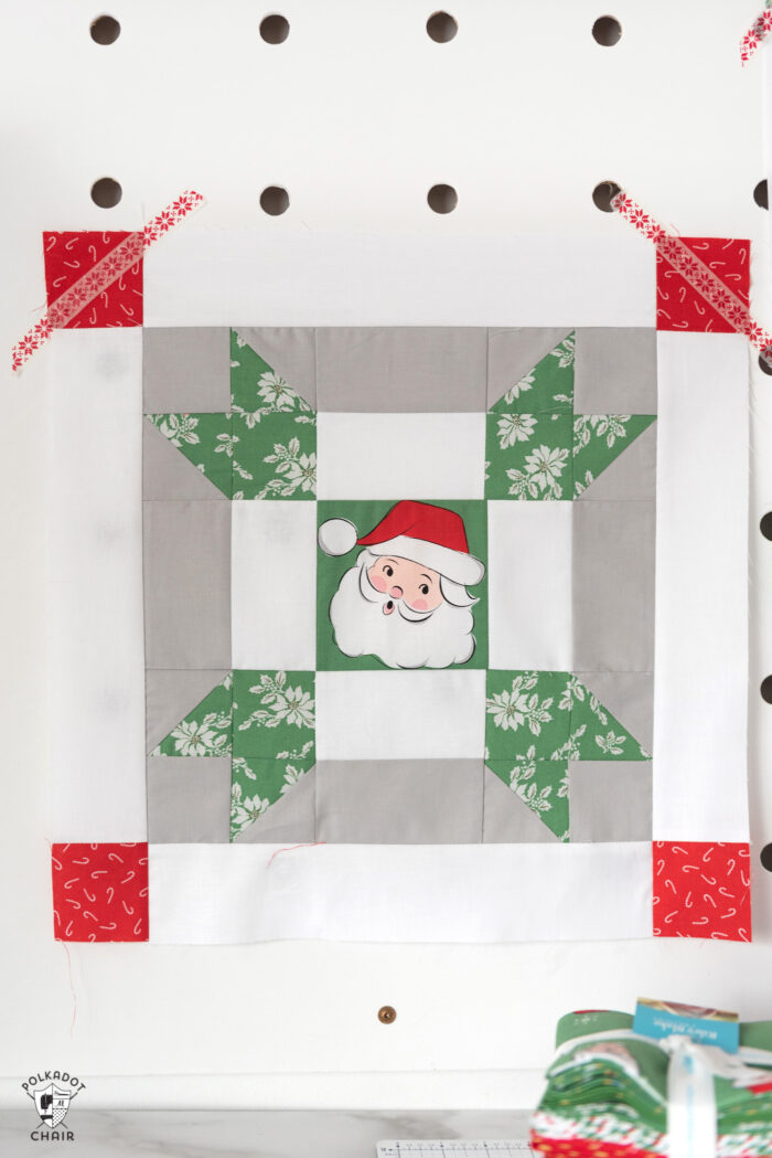 red and green christmas quilt blocks on peg board