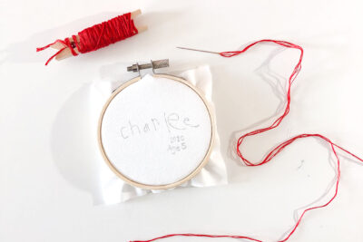 white fabric in embroidery hoop with red thread on a needle on white table