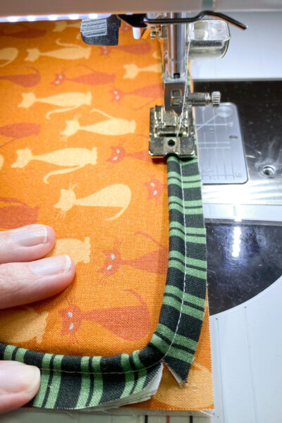sewing on piping to pillow front. orange pillow with green black piping