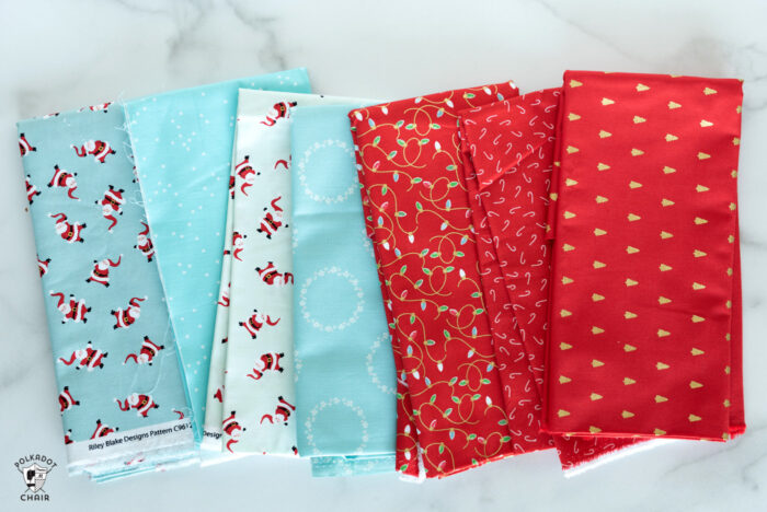 Christmas fabrics in reds and blues in stack on white marble tabletop