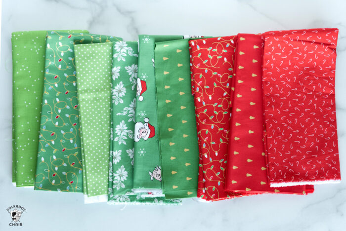 Christmas fabrics in reds and greens in stack on white marble tabletop