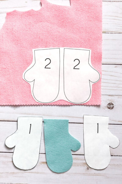 pieces of felt mitten cut out on white wood table