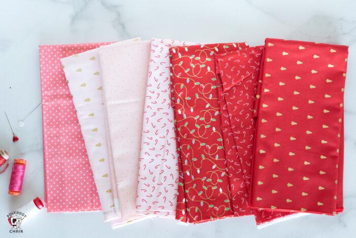 Christmas fabrics in reds and pinks in stack on white marble tabletop