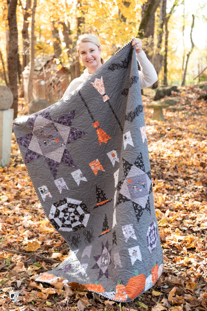 woman holding Halloween quilt outdoors