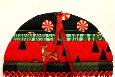 red, green and black christmas ornament in construction with batting on white table