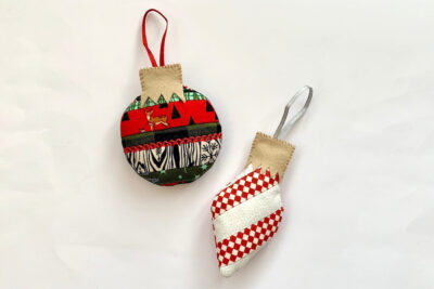 Finished scrappy Christmas ornament in red and green on white table