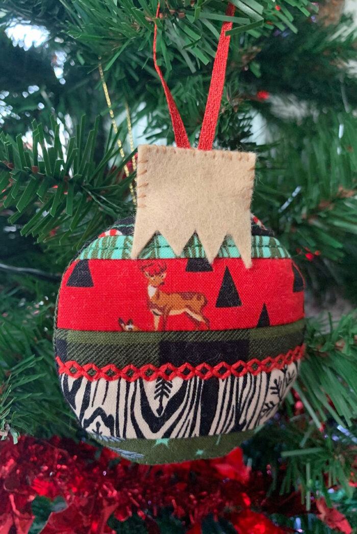 Finished scrappy Christmas ornament in red and green on Christmas Tree