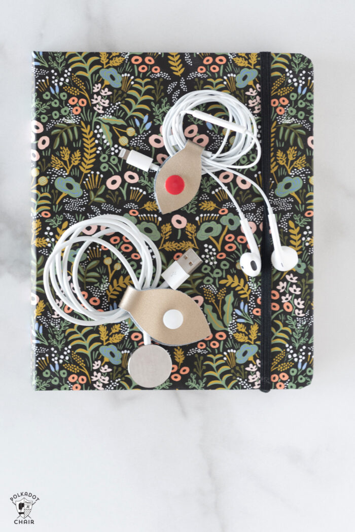 cord snaps around headphones on black floral book
