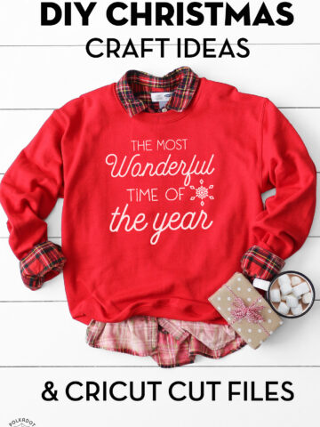 red sweatshirt with white lettering on white table with christmas props.