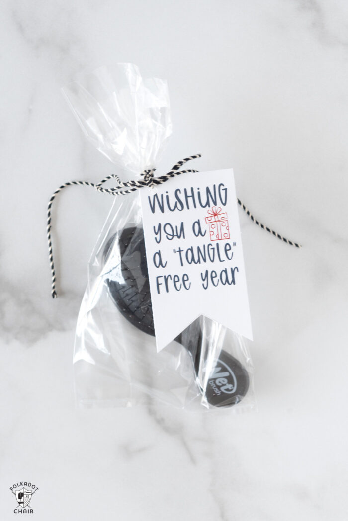 gift bags with a brush and tags on white marble table