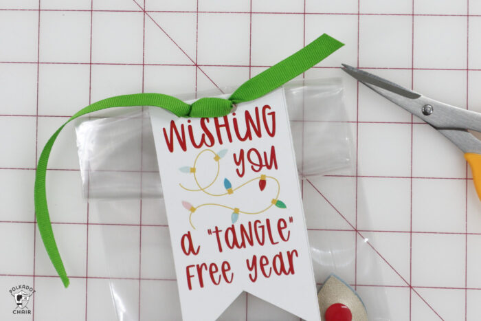 gift bags with cord snaps and tags on white marble table