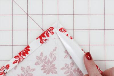 hand folding fabric on white cutting mat