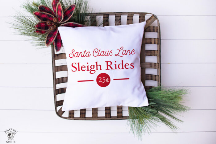 white pillow with red christmas lettering on white table with basket