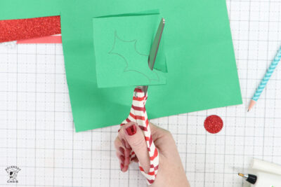scissors cutting green paper on white cutting mat