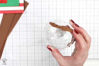 Christmas ornament with paper glued on on white cutting mat