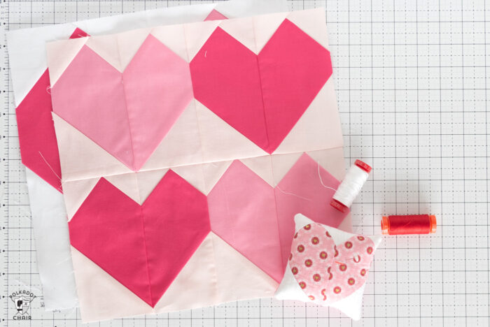 Pink and white heart quilt block on white cutting mat