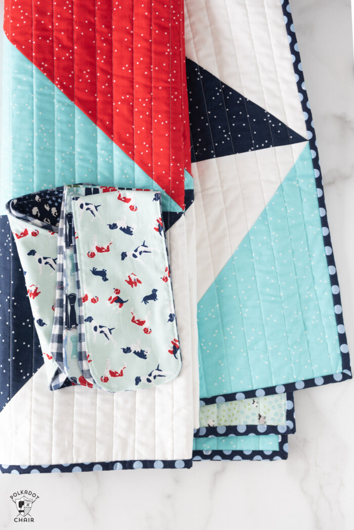 red white and blue baby quilt folded on white table