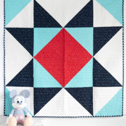 red white and blue baby quilt on white wall with toy in foreground
