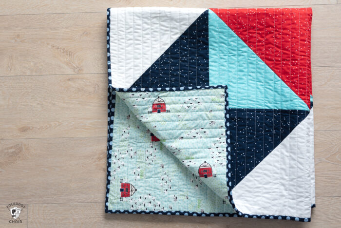 red white and blue baby quilt folded on wood floor