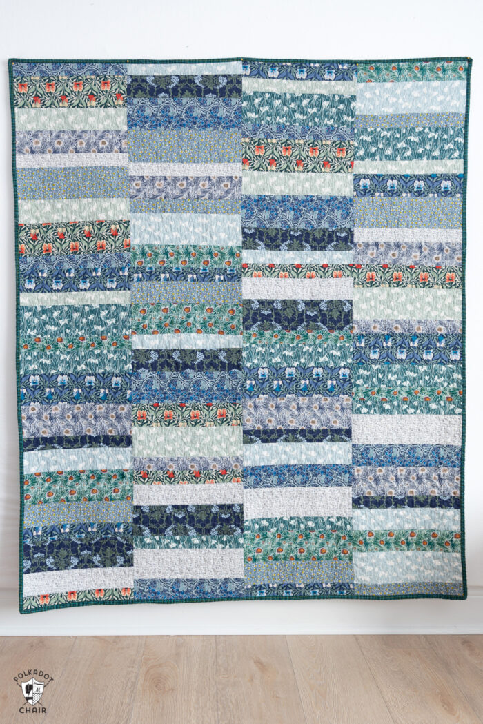 photo of a blue, green quilt on white wall