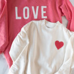 coral and ivory sweatshirts on white table