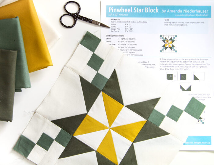 yellow and green quilt block from liberty of london fabrics on white cutting mat