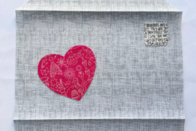 red heart and hand stitching on gray fabric