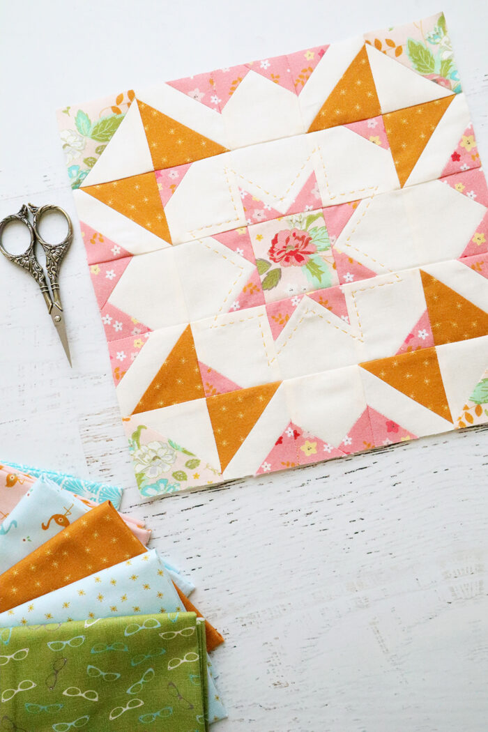 pink, orange and green quilt block on white table