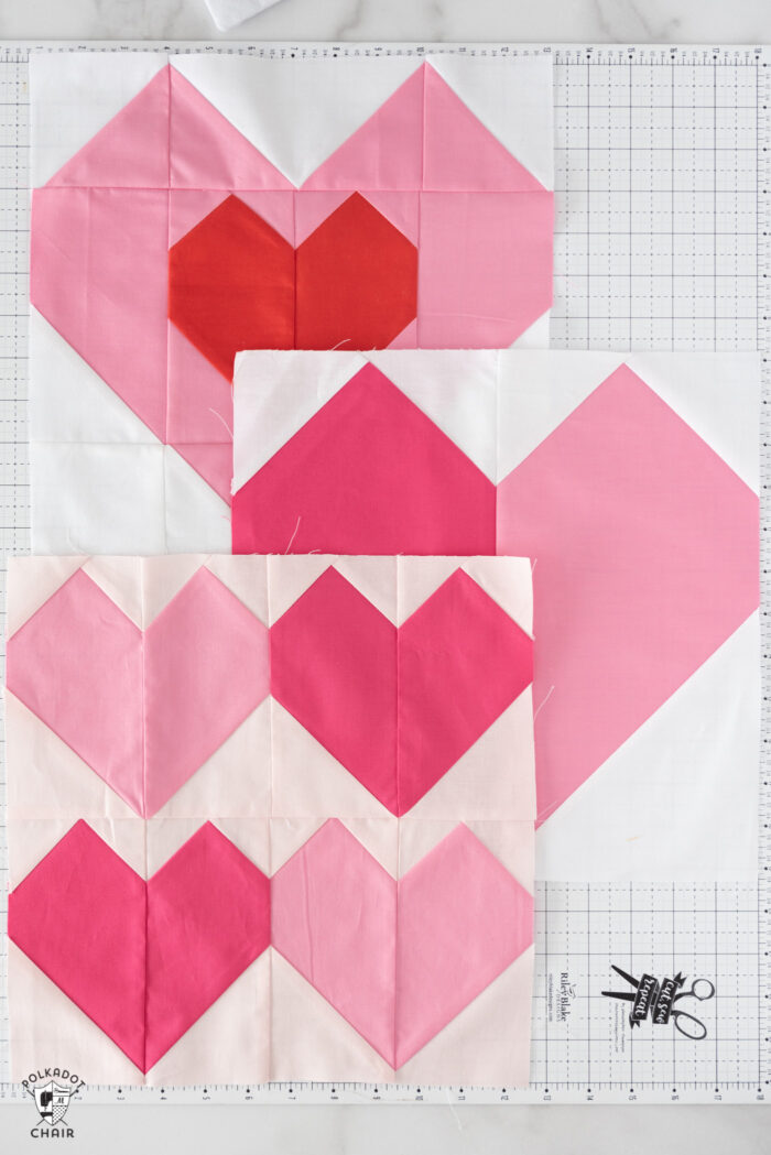 Pink and red heart quilt blocks on white cutting mat