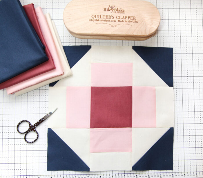 blue pink quilt blocks on white cutting mat