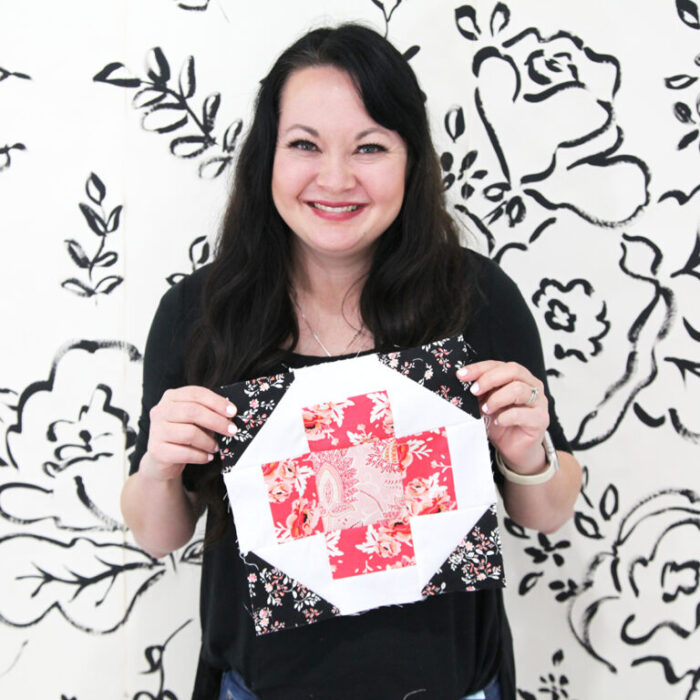 woman holding quilt block in front of white wall