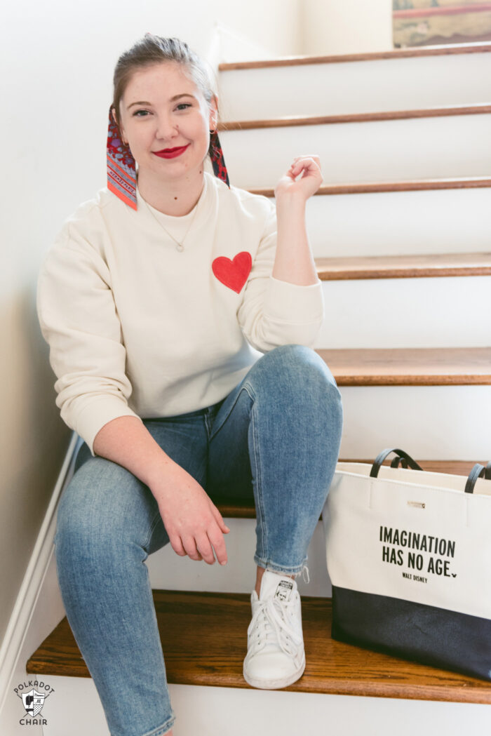 girl in ivory heart sweatshirt sitting on stairs