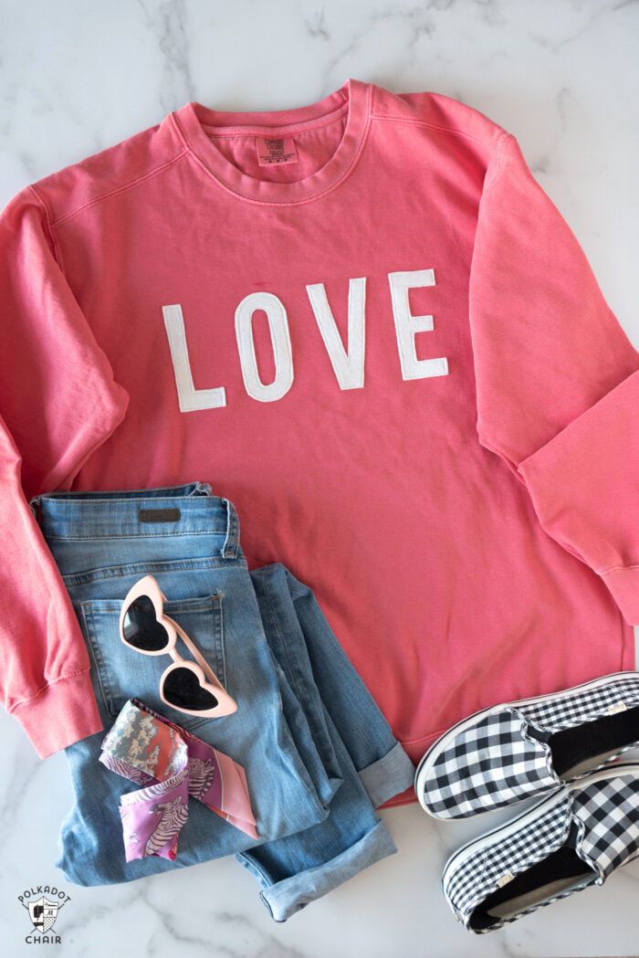 coral love sweatshirt, jeans and shoes on white table