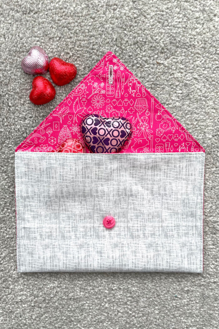gray and pink fabric envelope on gray carpet