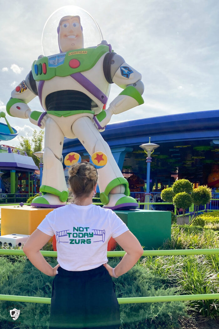 girl standing in front of ride at disneyworld