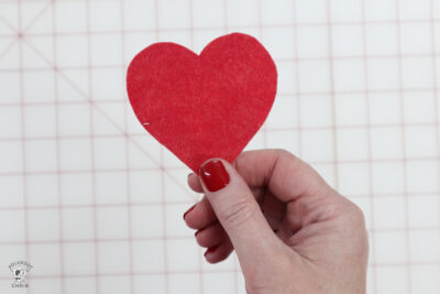 hand holding red cut out heart