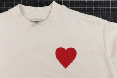 red heart on ivory shirt on black cutting mat