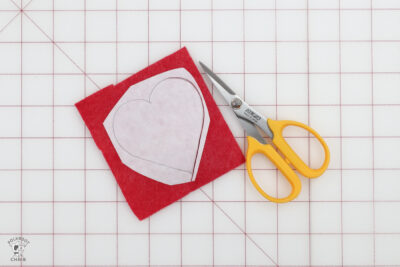 red felt and scissors on white cutting mat