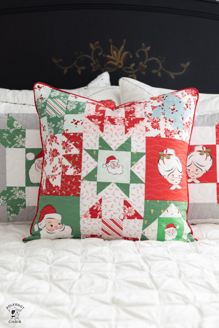 red, green and white patchwork christmas pillows on white bed