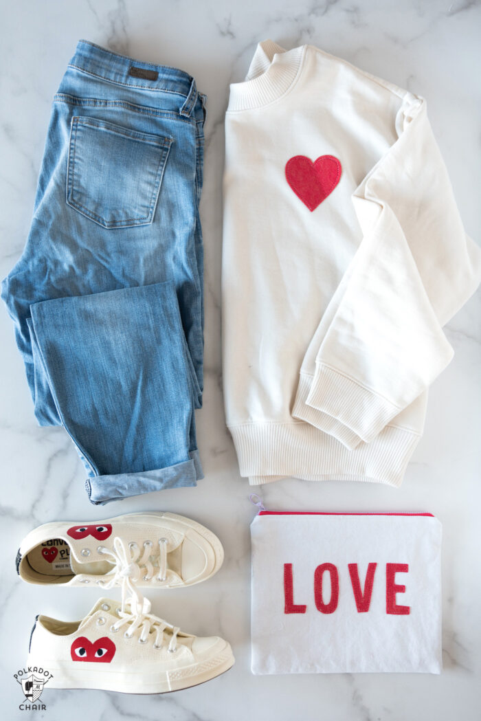 ivory sweatshirt, jeans and shoes on white table